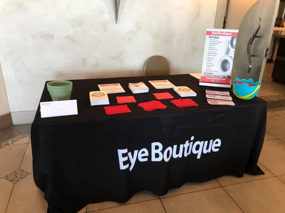 Table covered in black cloth with eyewear coupons and other information on printed cards